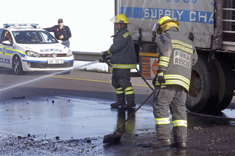 Firemen clear debris and fuel from the road, as Police provide security, left, after a truck was set alight by striking truck workers on a slipway off a main highway leading out of the city, near the international airport in Cape Town, South Africa, Friday, Oct 5, 2012. South African truck workers have been on strike for two weeks over wages, with sporadic violence reported and a number of trucks being set alight in past days. (AP Photo/Schalk van Zuydam)