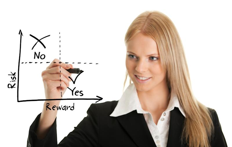 A young woman in a business suit drawing a risk versus reward chart.