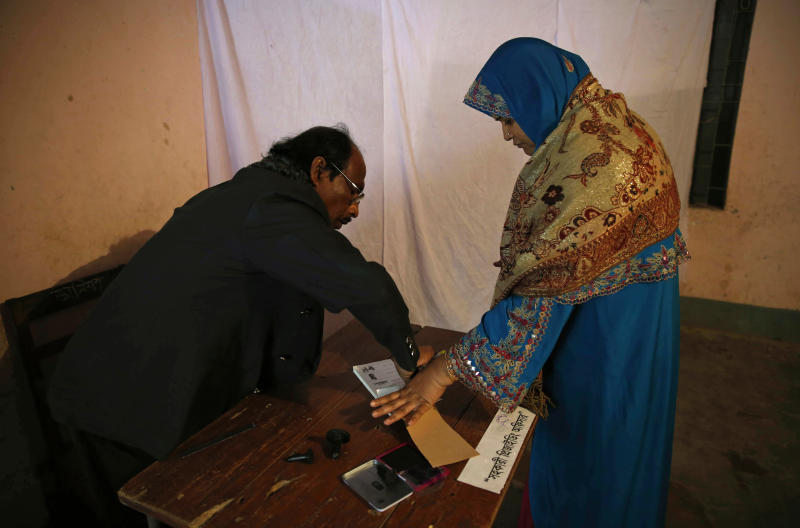 A Bangladeshi woman puts her thumb print to receive a ballot paper before casting her vote at a polling station in Dhaka, Bangladesh, Sunday, Jan. 5, 2014. Voting has started in Bangladesh for general elections Sunday that threaten to deepen the crisis in the South Asian nation. The opposition and its allies are boycotting the vote, a move that undermines the legitimacy of the election and makes it unlikely that the polls will stem a wave of political violence that killed at least 275 people in 2013. (AP Photo/ Rajesh Kumar Singh)