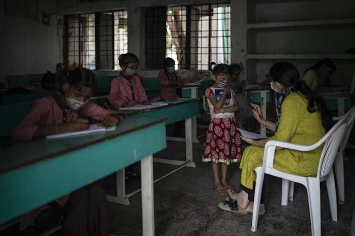 Students attend a class on the first day of partial reopening of schools in Noida, a suburb of New Delhi, India, Wednesday, Sept. 1, 2021. Many students in India will be able to step inside a classroom for the first time in nearly 18 months from Wednesday, as authorities have given the green light to partially reopen schools despite apprehension from some parents and signs that coronavirus infections are picking up again. Schools and colleges in least six states will reopen in a gradual manner with health measures in place throughout September. In New Delhi, all staff must be vaccinated and class sizes will be capped at 50% with staggered seating and sanitized desks. (AP Photo/Altaf Qadri)