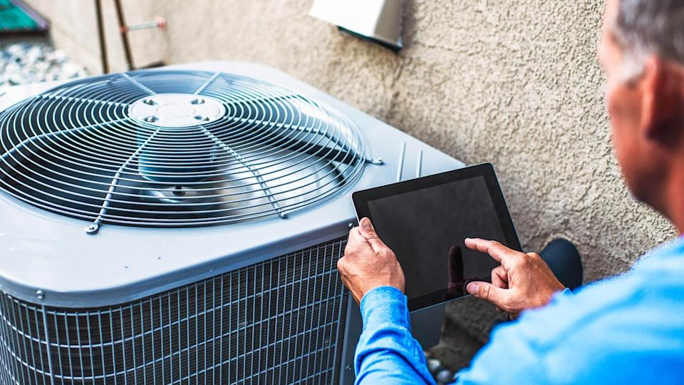 Maintenance engineer using digital tablet to inspect air conditioning unit.