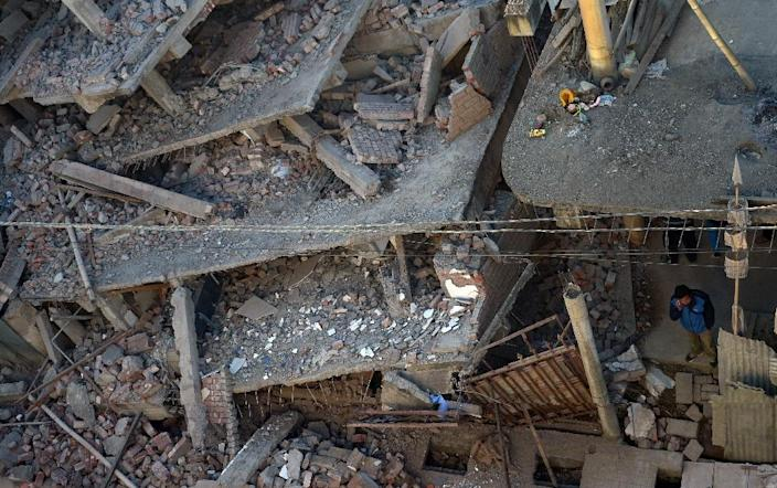 An Indian resident stands among buildings that were damaged when the strong 6.7 magnitude earthquake struck Imphal, on January 4, 2016 (AFP Photo/Dibyangshu Sarkar)