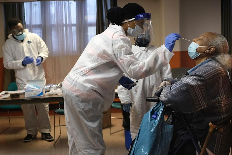 Mary Mack, right, a resident of senior housing, is tested for COVID-19 in Paterson, N.J., Friday, May 8, 2020. New York City is offering to test all nursing home residents and staffers for the coronavirus.