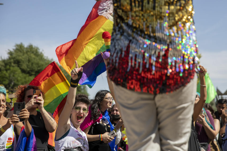 Participants dance in the annual Gay Pride parade in Jerusalem, Thursday, June 3, 2021. Thousands of people marched through the streets of Jerusalem on Thursday in the city's annual gay pride parade. (AP Photo/Ariel Schalit)