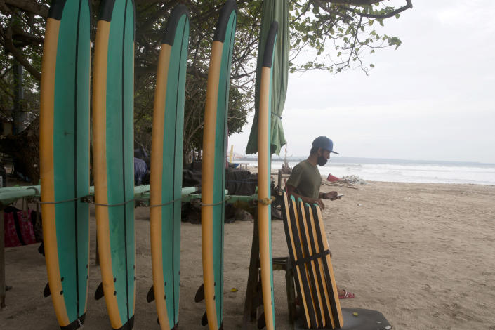 A man stands next to his surfboard stall as he waits for a costumer at a beach in Bali, Indonesia on Wednesday, Feb. 3, 2021. Amid fears of new variants of the virus, new restrictions on movement have hit just as people start to look ahead to what is usually a busy time of year for travel. (AP Photo/Firdia Lisnawati)
