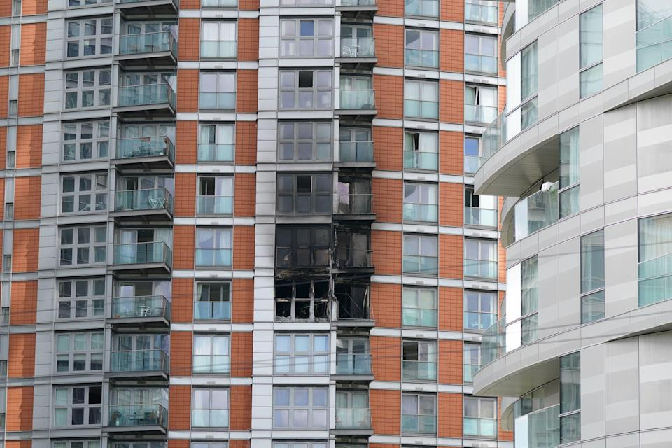 <p>Damage to a 19-storey tower block in New Providence Wharf, Canary Wharf, following a fire earlier in May</p> (PA)