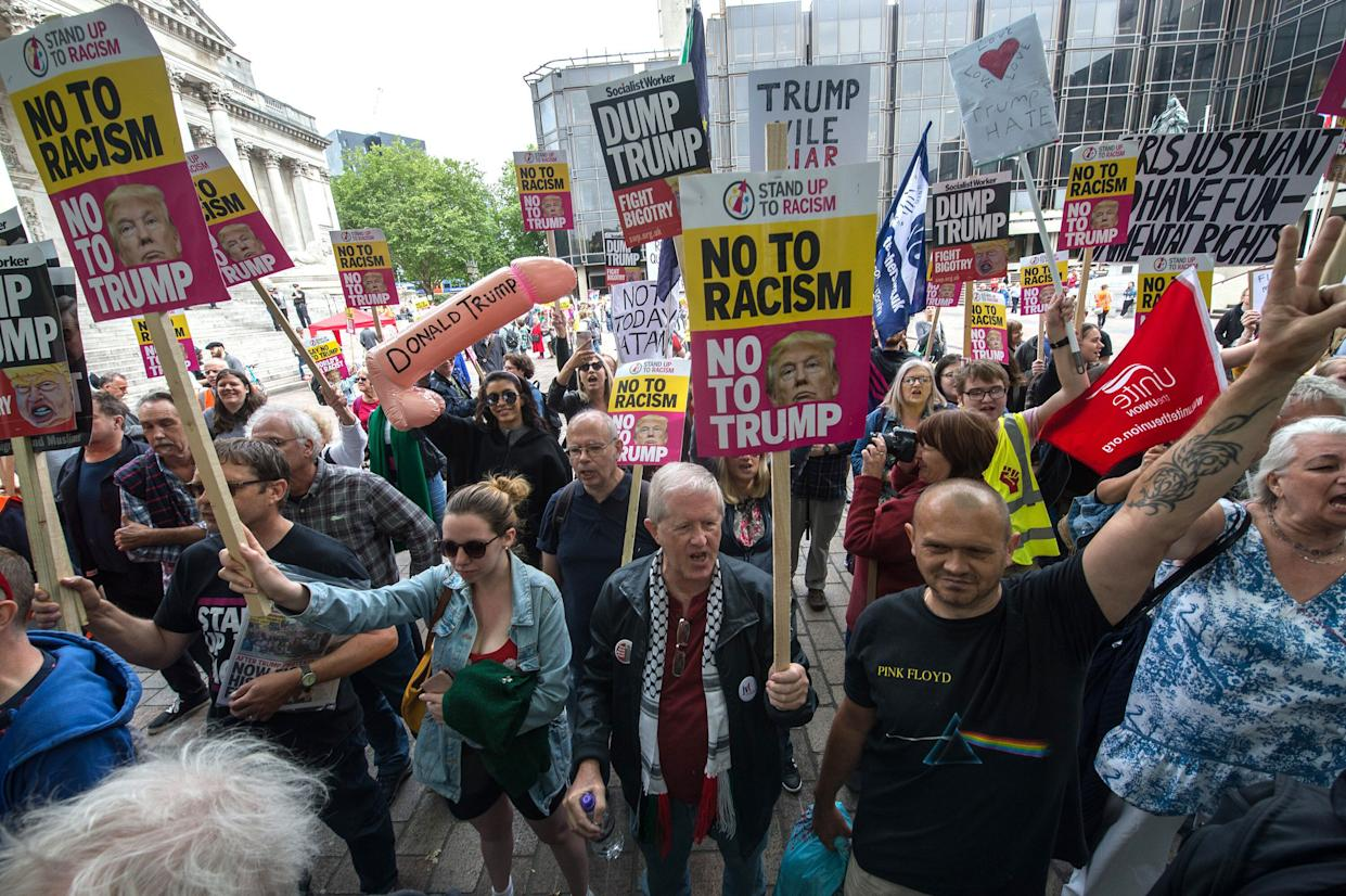 PORTSMOUTH, ENGLAND - JUNE 5: Protesters hold anti-Donald Trump signs in Guildhall Square on June 5, 2019 in Portsmouth, England. Activist groups under the banner Together Against Racism gather in Guildhall Square to demonstrate against the invitation of US President Donald Trump to the local D-Day commemoration. (Photo by Guy Smallman/Getty Images)