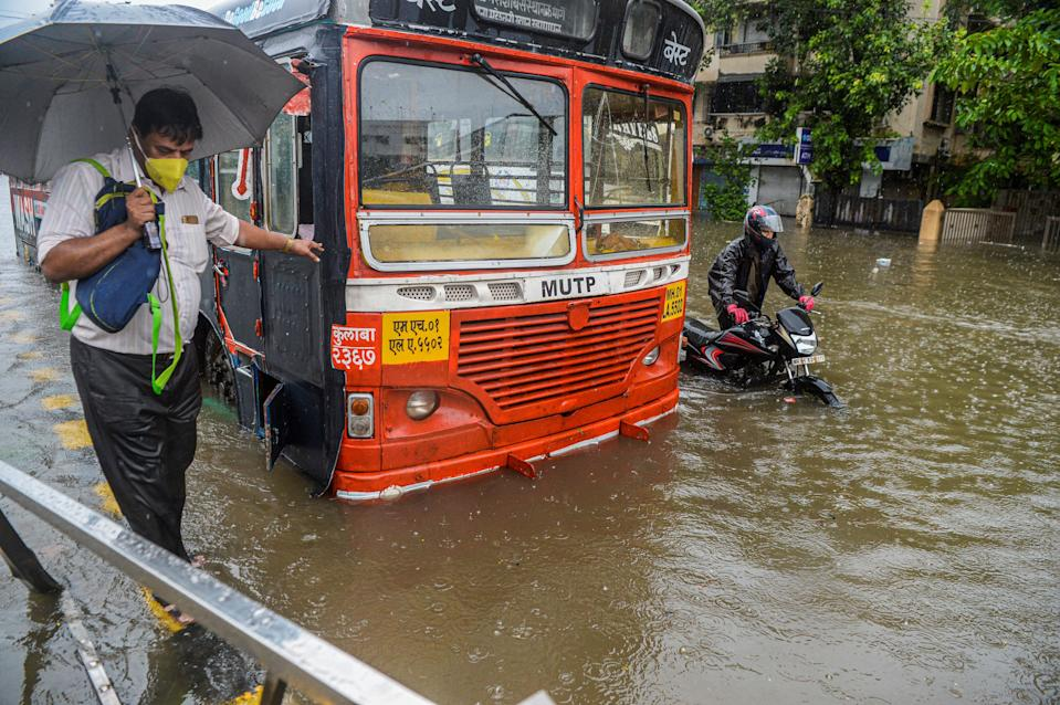 Commuters make their way through a flooded road during a heavy monsoon rain in Mumbai on August 4, 2020. (Photo by INDRANIL MUKHERJEE/AFP via Getty Images)