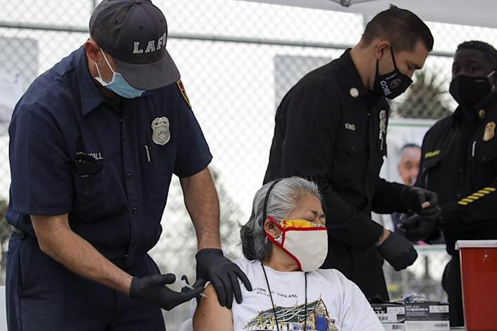 Firefighter Anthony MacDougall administers a COVID-19 vaccine to Carmen Limeta at a mobile vaccination site in L.A.