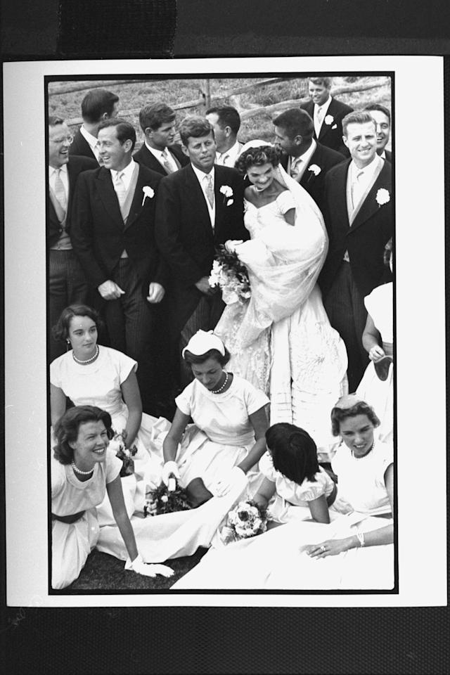 Sen. John Kennedy & his bride Jacqueline in their wedding attire, standing with 10 ushers incl. Teddy & Bobby Kennedy as 4 bridesmaids & flower girls sits on lawn in front of them while attempting to pose for group shot at their wedding. (Photo by Lisa Larsen//Time Life Pictures/Getty Images)