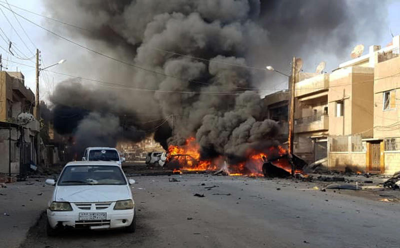 This photo by Hawar news, the news agency for the semi-autonomous Kurdish areas in Syria (ANHA), shows flames rising from burned cars at the site of an explosion in the central Qamishli city in northeastern Syria, Friday, Oct. 11, 2019. Activists and Syrian Kurdish officials are reporting a large explosion outside a popular fast food restaurant. It was not clear what caused the explosion on Friday which occurred amid intensive shelling by the Turkish military in the city and other areas. (ANHA via AP)