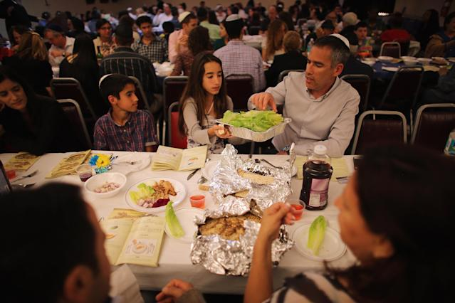 MIAMI BEACH, FL - MARCH 25: Omri Brandes, Nitzan Brandes and Bentsi Brandes (L-R) eat during a community Passover Seder at Beth Israel synagogue on March 25, 2013 in Miami Beach, Florida. The community Passover Seder that served around 150 people has been held for the past 30 years and is welcome to anyone in the community that wants to commemorate the emancipation of the Israelites from slavery in ancient Egypt. (Photo by Joe Raedle/Getty Images)