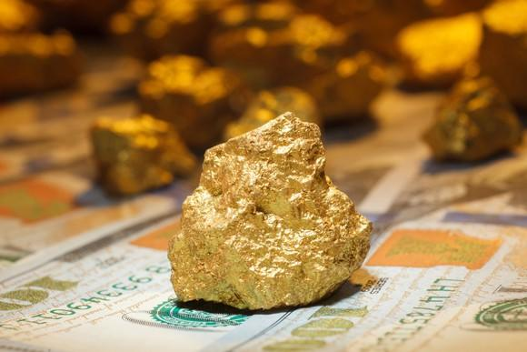 A big gold nugget sitting on top of hundred-dollar bills.