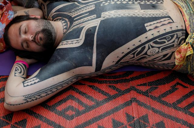 <p>A visitor to the London Tattoo Convention lies still as he has a tattoo drawn on his body with the hand-tapping method, in London, Britain, Sept. 23, 2017. (Photo: Peter Nicholls/Reuters) </p>