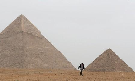 FILE PHOTO: A man walks in front of the Great Pyramids in Giza, on the outskirts of Cairo