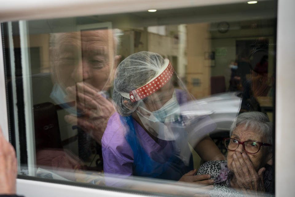 Javier Anto, 90, and his wife Carmen Panzano, 92, blow one another kisses through the window separating the nursing home from the street in Barcelona, Spain, Wednesday, April 21, 2021. Since the pandemic struck, a glass pane has separated _ and united _ Javier and Carmen for the first prolonged period of their six-decade marriage. Anto has made coming to the street-level window that looks into the nursing home where his wife, since it was closed to visits when COVID-19 struck Spain last spring. (AP Photo/Emilio Morenatti)