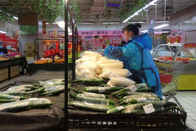 Employee sorts vegetables inside a supermarket in Wuhan, the epicentre of the novel coronavirus outbreak