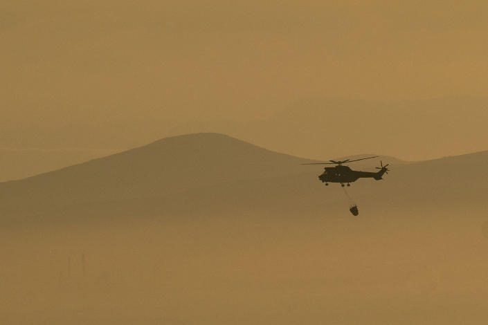 As smoke engulfs the South African city of Cape town, a South African Military helicopter ferries water used to control a massive fire spreading on the slopes of Table Mountain Tuesday, April 20, 2021. (AP Photo/Jerome Delay)
