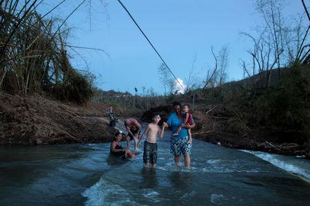 Local residents walk in a river after Hurricane Maria destroyed the town's bridge in San Lorenzo, Morovis, Puerto Rico, October 4, 2017. REUTERS/Alvin Baez