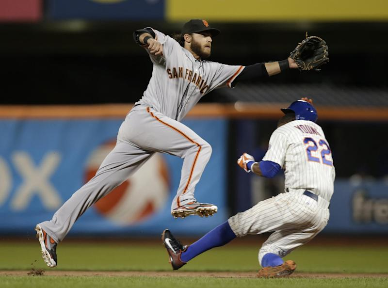 New York Mets' Eric Young Jr. (22) ducks as he steals second while San Francisco Giants shortstop Brandon Crawford (35) reaches for an errant throw from catcher Buster Posey in the first inning of a baseball game Tuesday, Sept. 17, 2013, in New York. Young reached third on the play. (AP Photo/Kathy Willens)