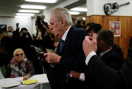 Czech President Milos Zeman arrives to cast a vote during the country's direct presidential election as a Femen activist is escorted by Zeman's bodyguards at a polling station in Prague, the Czech Republic January 12, 2018. REUTERS/David W Cerny
