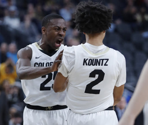 Colorado's McKinley Wright IV, left, celebrates with Daylen Kountz after a play against California during the first half of an NCAA college basketball game in the first round of the Pac-12 men's tournament Wednesday, March 13, 2019, in Las Vegas. (AP Photo/John Locher)