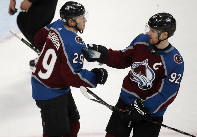 Colorado Avalanche center Nathan MacKinnon, left, is congratulated after scoring an empty-net goal by left wing Gabriel Landeskog in the third period of an NHL hockey game against the Vancouver Canucks Monday, Feb. 26, 2018, in Denver. The Avalanche won 3-1. (AP Photo/David Zalubowski)
