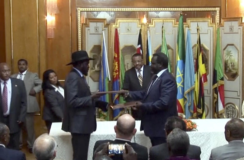 In this Friday, May 9, 2014 image made from video, South Sudan's President Salva Kiir, center left, and rebel leader Riek Machar, center right, exchange the signed documents in Addis Ababa, Ethiopia. The South Sudan's president has reached a cease-fire agreement with the rebel leader, an African regional bloc said Friday, after a vicious cycle of revenge killings drew international alarm. (AP Photo/AP Video)