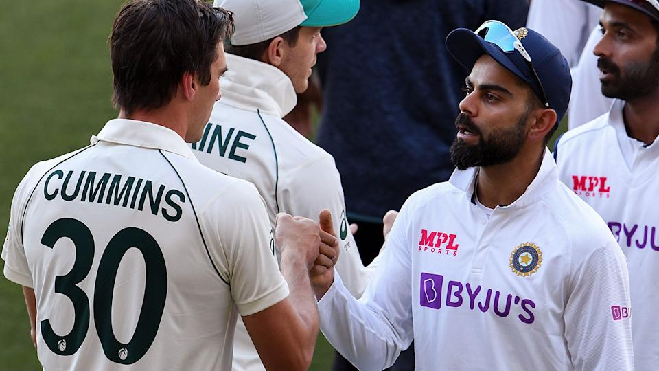 India's Virat Kohli congratulates Australia's Pat Cummins  after Australia's shock victory in the first Test. (Photo by WILLIAM WEST/AFP via Getty Images)