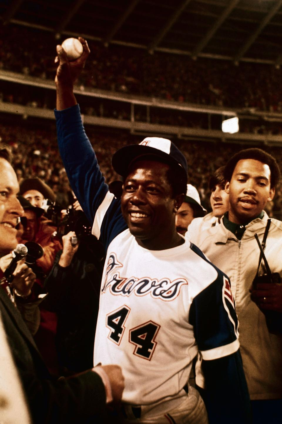 Hank Aaron holds up the ball here that broke Babe Ruth's home run record after he connected for his 715th career homer. With Aaron is his personal bodyguard, Calvin Wardlow. (Photo: Bettmann via Getty Images)