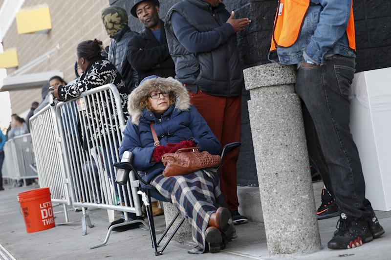 People wait in line to enter a Best Buy store in Westbury, New York