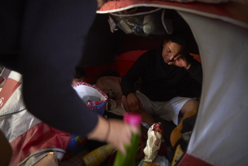 In this March 5, 2019, image, Juan Carlos Perla reacts as he and his wife, Ruth Aracely Monroy, left, searches for medicine in their tent for their 10-month-old son with a cold inside a shelter for migrants in Tijuana, Mexico. Many asylum seekers are now forced to wait in Mexico while their cases wind through U.S. immigration courts. (AP Photo/Gregory Bull)