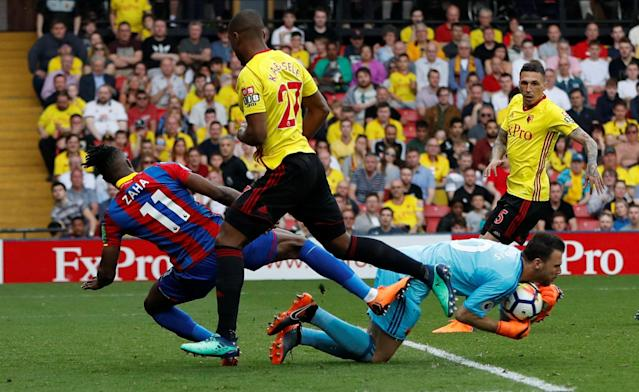 """Soccer Football - Premier League - Watford v Crystal Palace - Vicarage Road, Watford, Britain - April 21, 2018 Watford's Orestis Karnezis gathers from Crystal Palace's Wilfried Zaha Action Images via Reuters/Paul Childs EDITORIAL USE ONLY. No use with unauthorized audio, video, data, fixture lists, club/league logos or """"live"""" services. Online in-match use limited to 75 images, no video emulation. No use in betting, games or single club/league/player publications. Please contact your account representative for further details."""