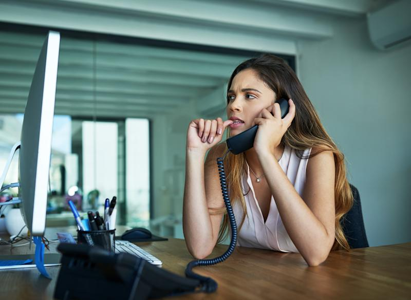 Shot of a young businesswoman biting her nails while talking on a phone in an office