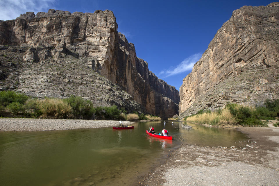 Far West Texas Outfitters owner and tour guide Mike Naccarato, left, leads a private river tour upstream on the Rio Grande in Santa Elena Canyon Wednesday, April 14, 2021, in Big Bend National Park, Texas. Santa Elena cliffs forming the canyon wall rise up to 1,500 feet from the Rio Grande according to the National Parks Service. (Jacob Ford/Odessa American via AP)