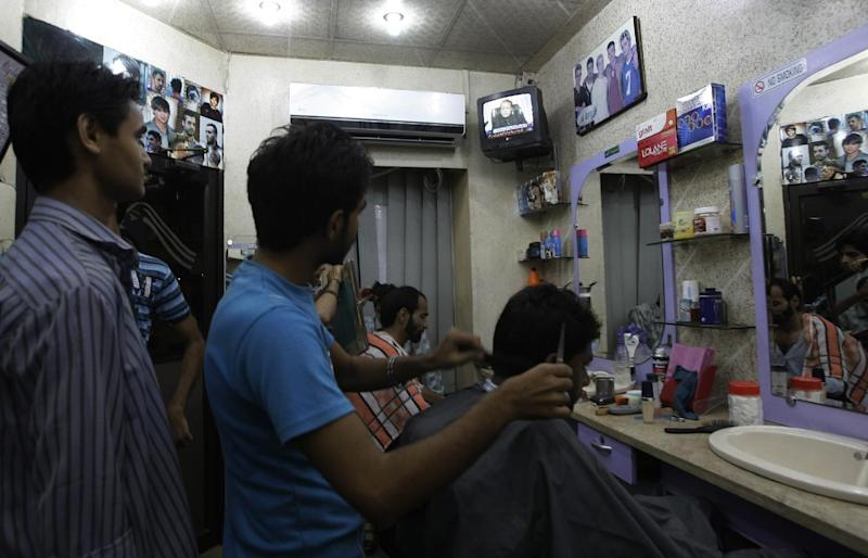 People watch Prime Minister of Pakistan Nawaz Sharif addressing the nation, at a barber shop in Karachi, Pakistan, Monday, Aug. 19, 2013. Sharif has reiterated his offer to talk with militants who have so far rejected the prospect of negotiations. But he also held open the possibility of new military operations against militants who have waged a campaign of bombings and shootings that have killed thousands of civilians and security personnel. (AP Photo/Fareed Khan)