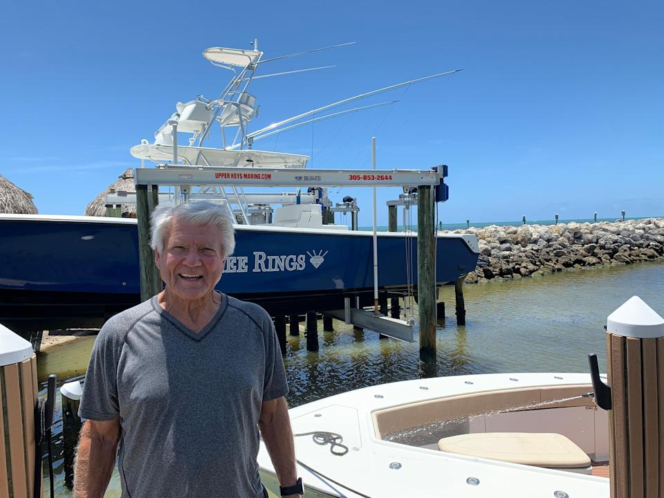 """Former Cowboys coach Jimmy Johnson in front of his fishing boat, """"Three Rings."""""""