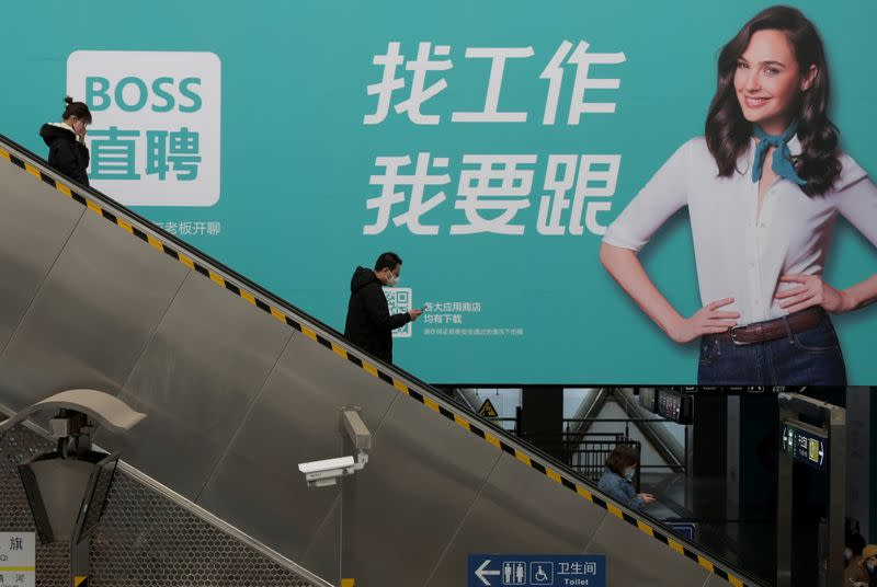 FILE PHOTO: People wearing face masks stand on an elevator down to the platform inside the Xierqi subway station, in the morning after the extended Lunar New Year holiday caused by the novel coronavirus outbreak, in Beijing