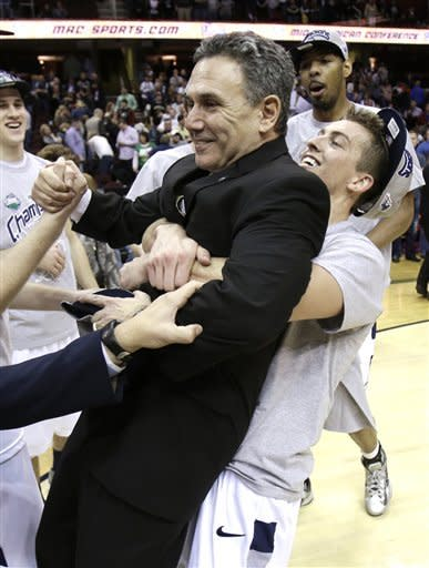 Akron's Brian Walsh, right, pick up head coach Keith Dambrot after Akron defeated Ohio 65-46 in an NCAA college championship basketball game in the Mid-American Conference tournament Saturday, March 16, 2013, in Cleveland. (AP Photo/Tony Dejak)