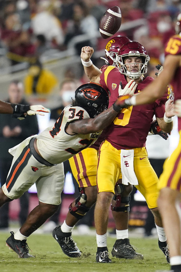 Southern California quarterback Kedon Slovis, right, loses the ball as he is hit by Oregon State linebacker Avery Roberts (34) during the second half of an NCAA college football game Saturday, Sept. 25, 2021, in Los Angeles. Oregon State recovered the ball on the play. (AP Photo/Marcio Jose Sanchez)