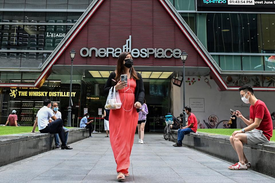 People seen outside the One Raffles Place commercial building on 9 June, 2021. (PHOTO: Getty Images)