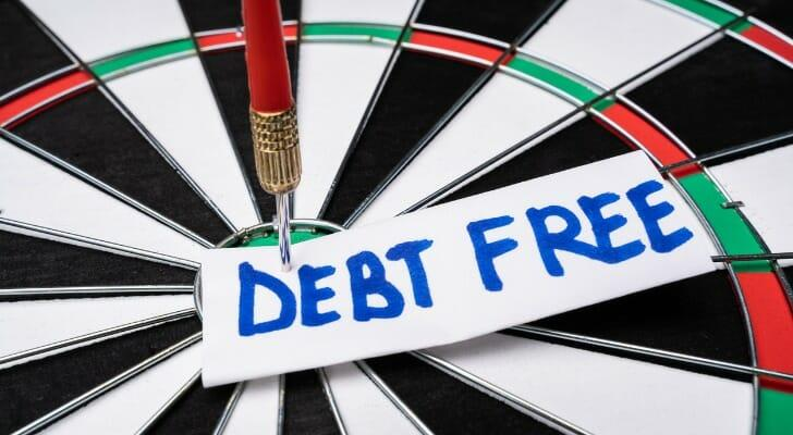 """Dart hits the bull's eye of a board labeled """"DEBT FREE"""""""
