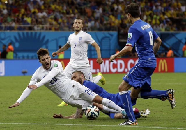 England's Adam Lallana, left, is fouled during the group D World Cup soccer match between England and Italy at the Arena da Amazonia in Manaus, Brazil, Saturday, June 14, 2014. Italy won the match 2-1. (AP Photo/Matt Dunham)