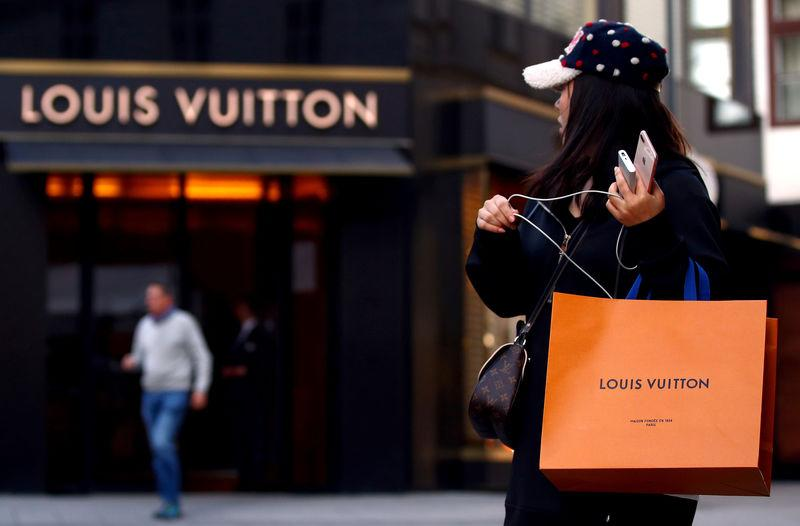 FILE PHOTO: Woman with a Louis Vuitton-branded shopping bag looks towards the entrance of a branch store by LVMH Moet Hennessy Louis Vuitton in Vienna