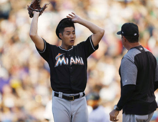 Miami Marlins starting pitcher Wei-Yin Chen, left, confers with pitching coach Juan Nieves after giving up an RBI-single to Colorado Rockies' Charlie Blackmon in the fourth inning of a baseball game Friday, June 22, 2018, in Denver. (AP Photo/David Zalubowski)