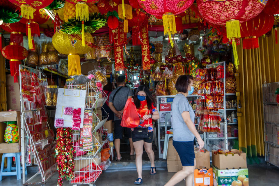 Customers walking out of religious goods store CYS Heong Trading Sdn Bhd in Taman Yulek, Cheras on Chinese New Year Eve, February 11, 2021. — Picture by Shafwan Zaidon