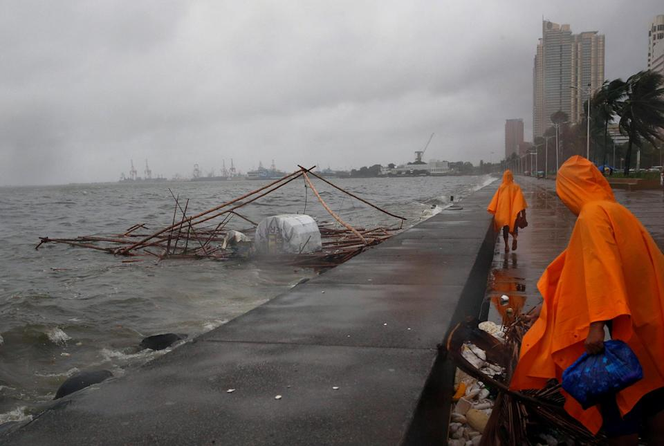 <p>Government workers walk near a capsized fishpen due to bad weather brought by typhoon Nepartak in Manila Bay, Philippines July 8, 2016. (REUTERS/Erik De Castro) </p>