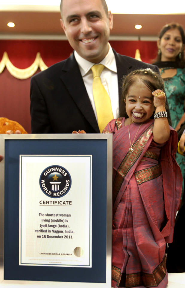 Jyoti Amge smiles after getting the title of the shortest woman by the Guinness World Records adjudicator Rob Molloy, in Nagpur, India, Friday, Dec. 16, 2011. Amge was declared the shortest woman in the world measuring 62.8 centimeters (24.7 inches) by the Guinness World Records. (AP Photo/ Manish Swarup)
