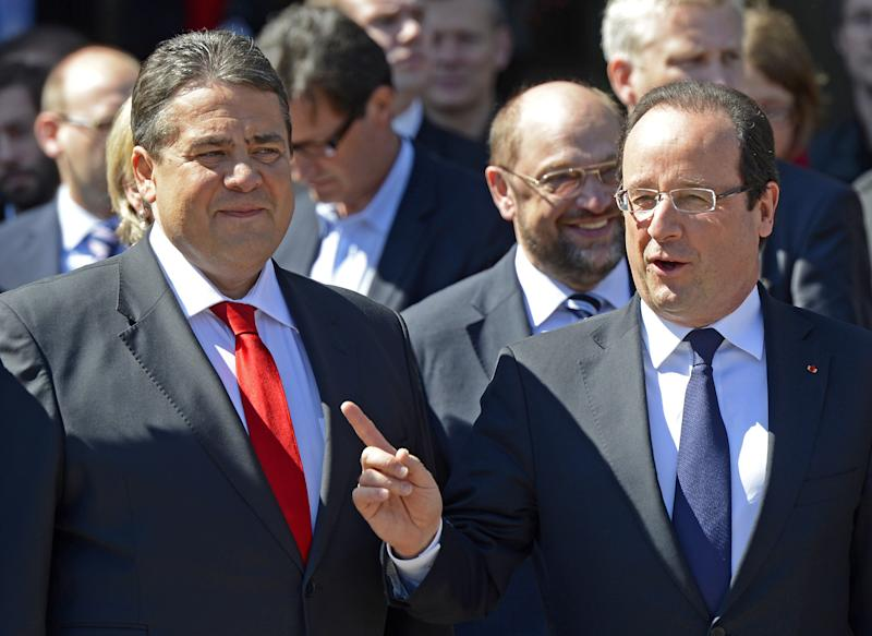 French President Francois Hollande, right, gestures next to Sigmar Gabriel, chairman of the German Social Democratic Party, SPD, left, in Leipzig, Germany, Thursday, May 23, 2013. Germany's main opposition party , SPD , is celebrating the 150th birthday. The Social Democratic Party is marking Thursday's anniversary with festivities in Leipzig, the eastern city where it was born in 1863. Guests include its main rival: popular conservative Chancellor Angela Merkel, who's just been named the world's most powerful woman by Forbes magazine for the third consecutive year. (AP Photo/Jens Meyer)