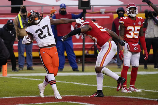 Cleveland Browns running back Kareem Hunt (27) celebrates in front of Kansas City Chiefs linebacker Anthony Hitchens, right, after scoring on a 3-yard touchdown run during the second half of an NFL divisional round football game, Sunday, Jan. 17, 2021, in Kansas City. (AP Photo/Jeff Roberson)